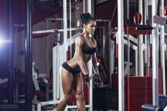 Brunetteeignungsmädchen in der schwarzen Sportabnutzung mit perfektem Körper in der Turnhalle Stockbilder
