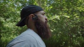 Brunettefrau, blaue Augen Ein grober Mann mit einem Bart läuft in den Wald stock footage