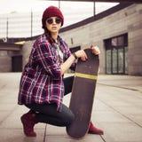 Brunettefrau in der Hippie-Ausstattung, die auf einem scateboard auf der Straße sitzt Getontes Bild Lizenzfreie Stockfotografie