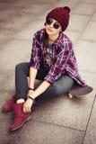 Brunettefrau in der Hippie-Ausstattung, die auf einem scateboard auf der Straße sitzt Getontes Bild Lizenzfreies Stockfoto