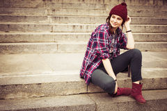 Brunettefrau in der Hippie-Ausstattung, die auf Schritten auf der Straße sitzt Getontes Bild Stockbilder