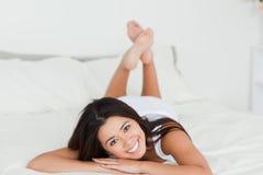 Brunettefrau, die auf Bett mit den gekreuzten Fahrwerkbeinen liegt Stockbilder