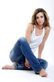 Brunettefrau, die auf dem Fußboden sitzt Stockfoto