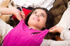 Brunettefrau, die auf dem Stapel der Kleidung lächelt natürlich aufwerfend, Einkaufsmodekonzept liegt Stockbilder