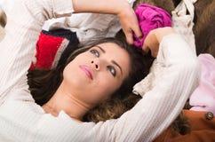 Brunettefrau, die auf dem Stapel der Kleidung lächelt natürlich aufwerfend, Einkaufsmodekonzept liegt Stockbild