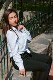 Brunettefrau, die auf der Bank mit Parkhintergrund sitzt lizenzfreies stockfoto