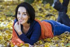 Brunettefrau, die auf Herbsthintergrund lächelt Stockbilder