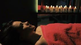 Brunettefrau, die auf Massagetabelle in Schönheitssalon Nahaufnahme liegt stock video