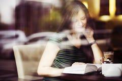 Brunettefrau, die am Cafélesungsbuch-, Studing und Trinkenkaffee sitzt Stockbild