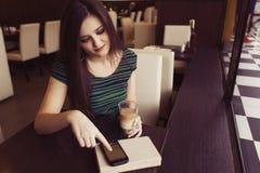Brunettefrau, die am Cafélesungsbuch-, Studing und Trinkenkaffee sitzt und jemand wartend, das spät ist Lizenzfreie Stockfotos