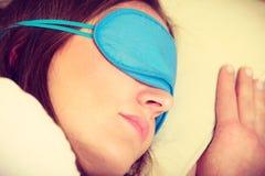 Brunettefrau, die in der Schlafmaske des blauen Auges schläft Lizenzfreies Stockbild