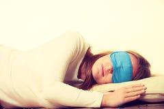 Brunettefrau, die in der Schlafmaske des blauen Auges schläft Stockfoto