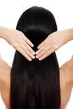 Brunettefrau, die ihr Haar berührt Stockfoto