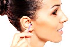 Brunettefrau, die ihr Ohr säubert stockfotografie