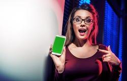 Brunettefrau, die ihren Smartphone verwendet stockfoto