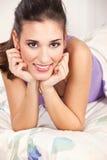 Brunettefrau, die im Bett liegt Stockfotografie