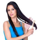 Brunettefrau, die langes Haar kämmt Lizenzfreie Stockbilder