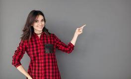 Brunettefrau, die mit ihrem Finger zum Kopienraum darstellt Stockbilder