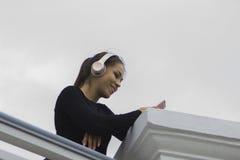 Brunettefrau, die Musik in den Kopfhörern hört und genießt Stockbild