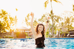 Brunettefrau, die Wasser im sexy Bikini am Pool spritzen lässt Nehmen Sie die bräunende Frau des Sitzes ab, die Spaß im Pool hat Lizenzfreies Stockbild