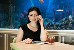 Brunettefrau, die zuhause auf einem Mobiltelefon spricht Lizenzfreie Stockfotos