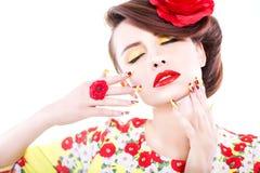 Brunettefrau im gelben und roten Kleid mit Mohnblumenblume in ihrem Haar, in Mohnblumenring und in kreativen Nägeln, geschlossene Lizenzfreie Stockbilder