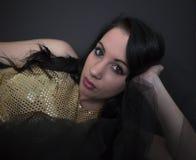 Brunettefrau im Goldkleid lizenzfreie stockfotografie