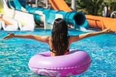 Brunettefrau im Gummiring im Swimmingpool lizenzfreie stockfotos
