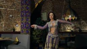 Brunettefrau im lila Kostüm tanzt Bauchtanz im Restaurant stock video footage