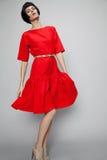 Brunettefrau im roten Kleid Lizenzfreies Stockfoto