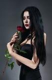 Brunettefrau im schwarzen Kleid mit Rot stieg Stockfoto