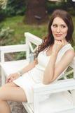 Brunettefrau im weißen Kleid, das auf Bank im Park sitzt Lizenzfreie Stockbilder
