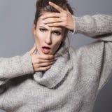 Brunettefrau mit Brötchenfrisur und neutrale Person bilden herein aufwerfen Stockfoto