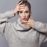 Brunettefrau mit Brötchenfrisur und neutrale Person bilden herein aufwerfen Stockfotografie