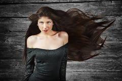 Brunettefrau mit dem langen Haar über hölzernem Hintergrund Stockbild