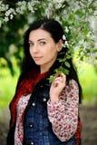 Brunettefrau mit dem langen Haar unter Kirschbaum in der Blüte Stockfoto