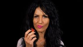 Brunettefrau mit den sinnlichen Lippen eine köstliche Erdbeere essend stock video