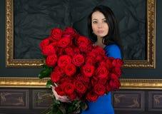 Brunettefrau mit einem großen Blumenstrauß von roten Rosen Stockfotos