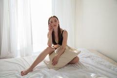 Brunettefrau, nachdem sie im Schlafzimmer geschlafen hat, pillows auf dem Bett lizenzfreie stockbilder