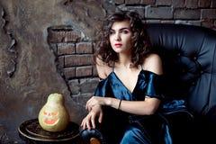 Brunettefrau sitzt im Weinleseledersessel Ein grimmiger Minireaper, der eine Sense anhält, steht auf einem Kalendertag, der glück lizenzfreies stockbild