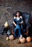 Brunettefrau sitzt im Weinleseledersessel Ein grimmiger Minireaper, der eine Sense anhält, steht auf einem Kalendertag, der glück stockfotografie