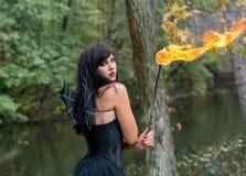Brunettefrauen mit Halloween-Hexenmake-up steht mit einer Fackel I Lizenzfreie Stockbilder