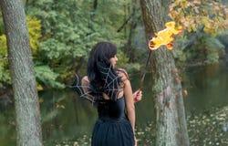 Brunettefrauen mit Halloween-Hexenmake-up steht mit einer Fackel I Lizenzfreie Stockfotografie