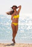 Brunettefrauengelb-Badeanzugmeer Lizenzfreie Stockbilder