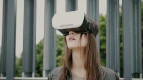 Brunettefrauenmädchen mit dem wellenartig bewegenden Haar benutzt Gläser der virtuellen Realität im Stadtgebiet Lizenzfreie Stockbilder
