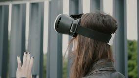 Brunettefrauenmädchen mit dem wellenartig bewegenden Haar benutzt Gläser der virtuellen Realität im Stadtgebiet 4K Stockfoto