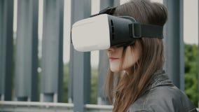 Brunettefrauenmädchen mit dem wellenartig bewegenden Haar benutzt Gläser der virtuellen Realität im Stadtgebiet 4K Lizenzfreie Stockfotos