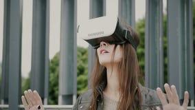 Brunettefrauenmädchen mit dem wellenartig bewegenden Haar benutzt Gläser der virtuellen Realität im Stadtgebiet 4K Lizenzfreie Stockbilder
