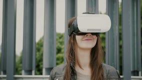 Brunettefrauenmädchen mit dem wellenartig bewegenden Haar benutzt Gläser der virtuellen Realität im Stadtgebiet 4K Lizenzfreie Stockfotografie