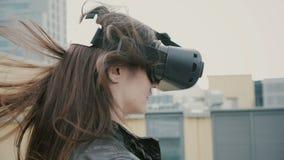 Brunettefrauenmädchen mit dem wellenartig bewegenden Haar benutzt Gläser einer virtuellen Realität auf dem Dach Stockfotografie